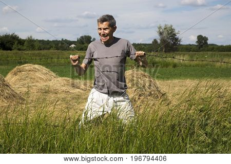 A man tries to break a barbed wire with his hands