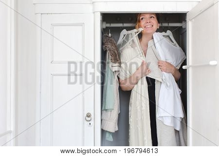 A woman laughs while choosing clothes while she is in the closet. A woman is overwhelmed in a closet of messy clothes for a style or fashion concept.