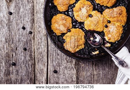 Homemade Blueberry cobbler in a cast iron skillet pan on a rustic wooden table. Organic natural food. Healthy breakfast. Top view. Selective focus