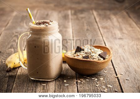 Banana chocolate smoothie and muesli on wooden table