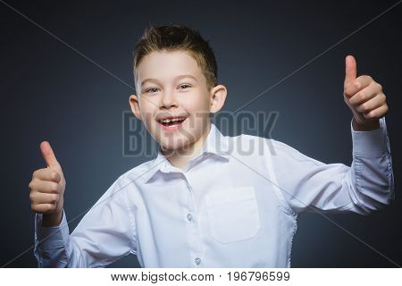 Closeup portrait successful happy boy show thumb up isolated grey background