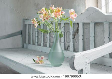 the alstroemeria in vase onold wooden bench