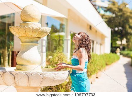 Pretty young woman enjoy the cold water of open street fountain in hot summer day