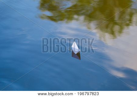 One paper boat sailing on blue water surface of lake