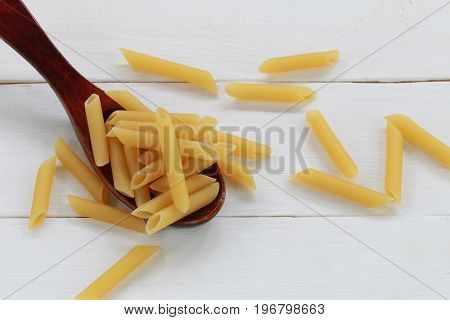 Raw Macaroni in the wooden spoon on wood background for design in your work.