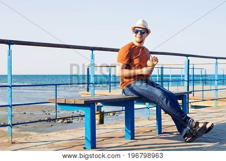 Portrait of cheerful attractive bearded hipster young man drinking iced coffee or frappe on the background of the sea.