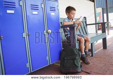 Boy using mobile phone while sitting on bench by lockers in corridor at school