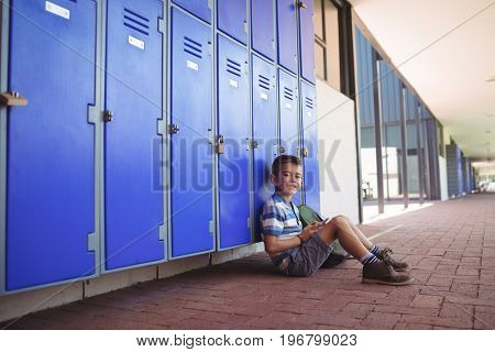 Portrait of smiling boy sitting by lockers in corridor at school