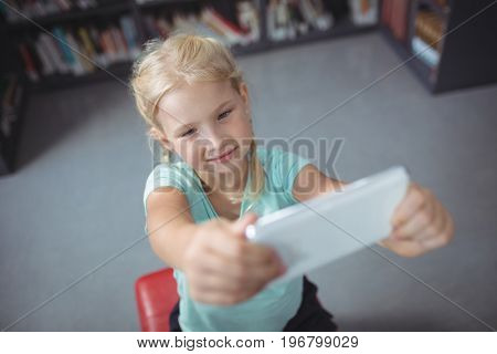 High angle view of girl using mobile phone while sitting in library