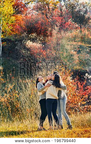 Group of happy young women hugging in autumn forest