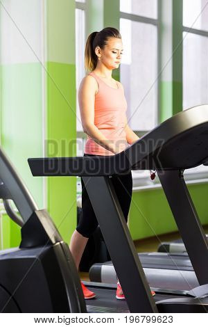 sport, fitness, lifestyle, technology and people concept - smiling woman exercising on treadmill in gym.