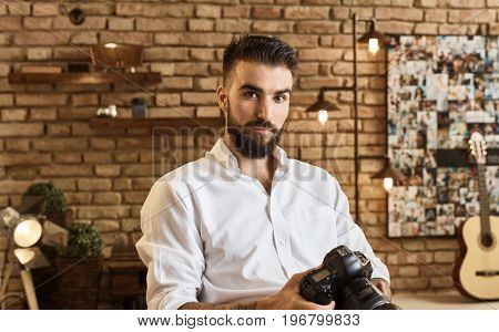 Portrait of bearded young man holding camera at trendy industrial loft home. Photographer portrait.