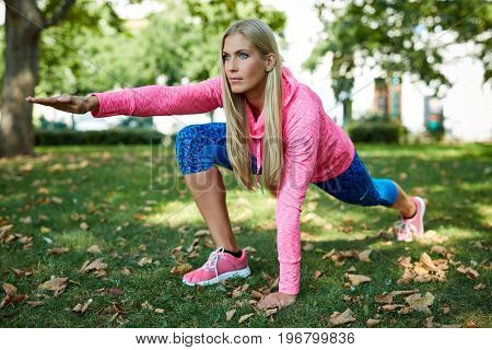 Young woman doing yoga exercises at citypark.