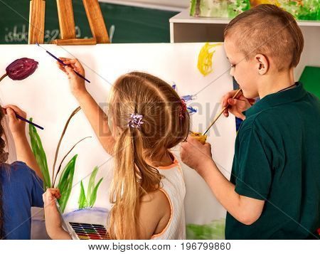 Children painting on easel. Girl with boy learn paint in class school. Child picture on background. Preparing for a children's art exhibition.