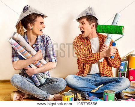 Repair family by happy couple building home. Quarrel family because of renovation in new apartment. Mad woman and man in newspaper cap renovation apartment by painting tools Newlyweds in the new house