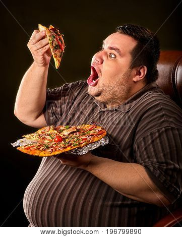 Failure of fat man eating fast food slice pizza on plate. Close up of breakfast for hungry overweight person who spoiled healthy food. Junk meal leads to obesity. Poor food leads to obesity.