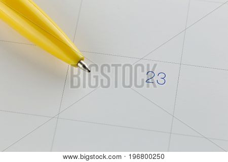 yellow pen points to the number 23 on calendar background in concept of appointment schedules and important dates.