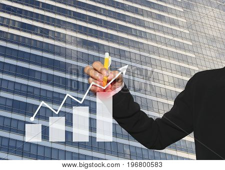 hand of business woman using yellow pen write business graph on tall building background in concepts profit and investment.