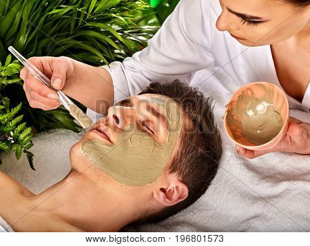 Mud facial mask of man in spa salon. Massage with clay full face. Girl on with therapy room. Man lying wooden spa bed. Healing clay to preserve youth. Close-up of a man's face.