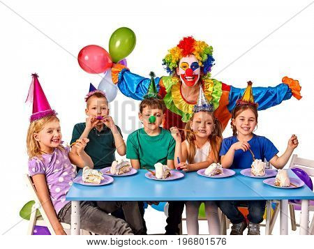 Birthday child clown playing with children who eat cake. Kid with nose bunny fingers prank. Fun of group people pose for camera sit at table white background. Holiday in a children's club.
