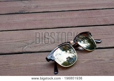 Sunglasses on wooden brown surface with room for text.
