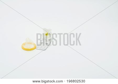 Emergency contraceptive pills condom and flower on white background