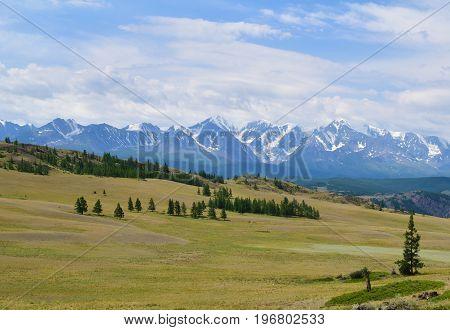 Scenic view of Kurai steppe andwhite peaks of North-Chiyski ridge in Altai mountains in overcast weather. Altay Republic Siberia Russia.