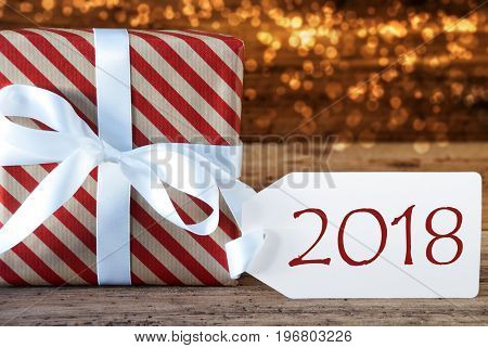 Macro Of Christmas Gift Or Present On Atmospheric Wooden Background. Card For Seasons Greetings, Best Wishes Or Congratulations. White Ribbon With Bow. Text 2018 For Happy New Year