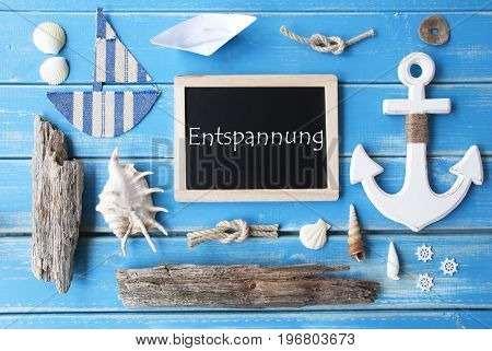 Flat Lay Of Chalkboard On Blue Wooden Background. Nautic Or Maritime Summer Decoration As Holiday Greeting Card. German Text Entspannung Means Relaxation