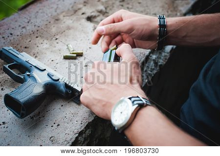 Man Charges Clip Of Pistol With Bullets. Photo Hands Of Paramilitary, Reloading Weapons. Preparation