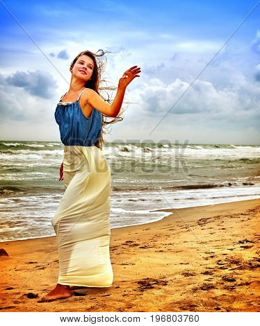 Woman on beach in sunset on sand. Teenager girl on sea shore. Summer style outfit sitting near ocean. Girl on an uninhabited island. Girl flew off her hat.