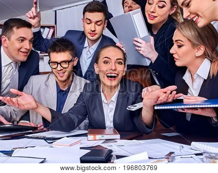 Business people office life of team people are happy with hand up sitting table and working papers. Cabinets with folders and jalousie background. Preventing economic crisis.