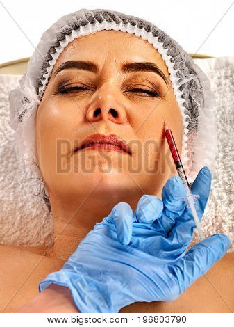 Filler injection female face. Plastic facial surgery in beauty clinic. Eelderly woman of 50-60 years takes care of her appearance. Doctorwith syringe injects try removal of wrinkles. poster