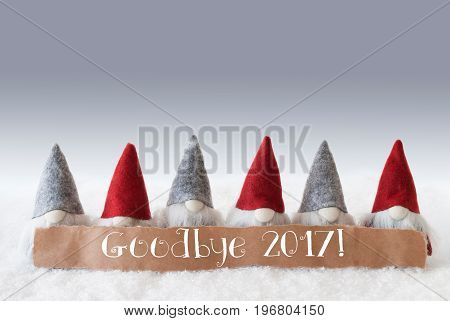Label With English Text Goodbye 2017 For Happy New Year. Christmas Greeting Card With Gnomes. Silver Background With Snow.