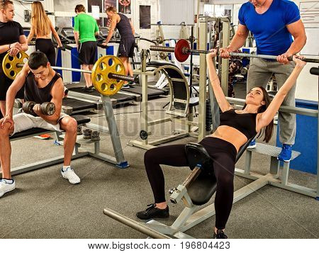Fitness friends workout gym. Woman working on bench press. She lifting barbell. Man backs girl while taking exercises. Group work people on background. Girl watches her figure.