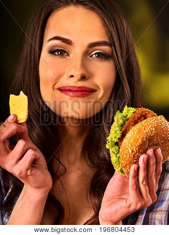 Woman eating hamburger. Portrait of student consume fast food . Girl trying to eat junk. Advertise fast food on dark background. Supper of busy person idea.