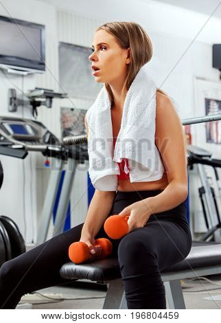 Woman holding dumbbell workout at gym. Weights for women. Middle section of bare belly. Treadmill on background. Body that you want concept. Girl is tired in training.