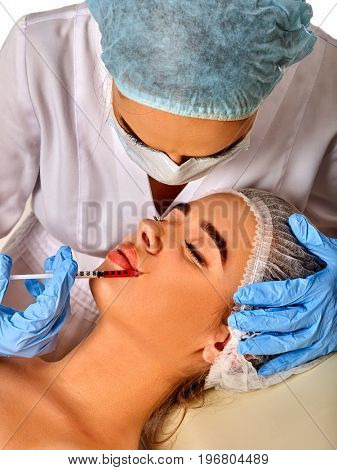 Filler injection for female forehead face. Plastic aesthetic facial surgery in beauty clinic. Pretty woman giving injections. Doctor in medical gloves with syringe injects nasolabial fold drug.