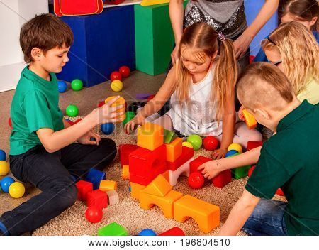 Children building blocks in kindergarten. Group kids playing toy on floor. Top view of interior preschool. Children develop their fingers in a game of cubes. Children are friends in team.