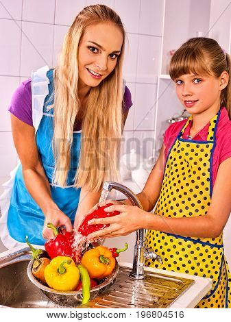 Fruit and vegetable wash of woman with daughter on kitchen home. Girl washing vegetables under pouring water tap in colander sink indoor. Fighting bacteria idea.