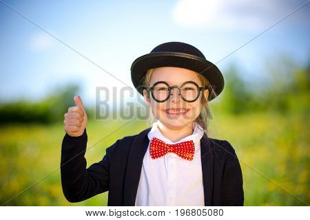 Funny little girl in bow tie and bowler hat showing thumb up. Retro stile.