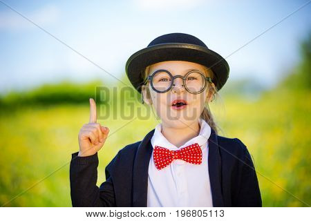 Funny little girl in glasses, bow tie and bowler hat pointing finger up. Retro stile.