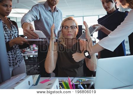 Irritated businesswoman sitting amidst team holding technologies at office