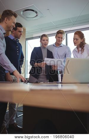 Happy young business colleagues discussing around desk in metting room