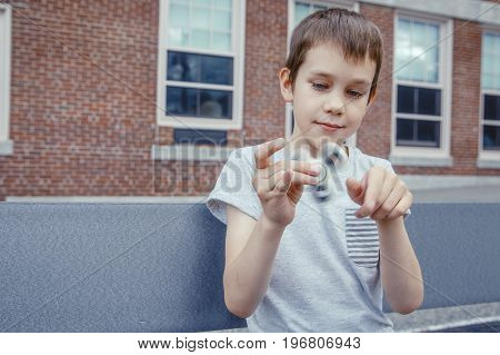 boy fascinated by the game with the  fidget spinner. satisfied kid plays with a spinner on the schoolyard