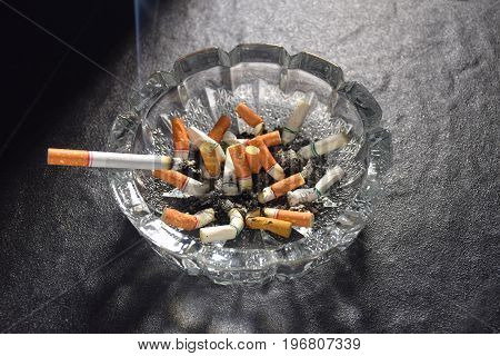 Lit cigarette with smoke lying on an ashtray filled with cigarette butts and ashes