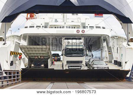 Norwegian car ferry landing at port. Open barrier. Horizontal