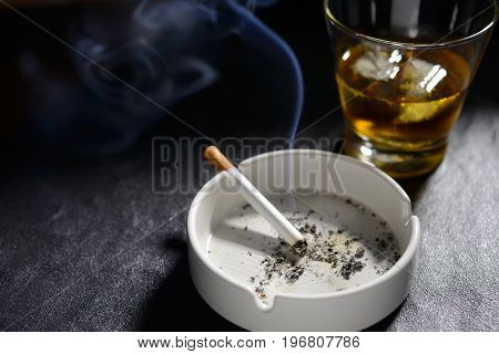 Lit and smoking cigarette in ashtray with glass of whiskey