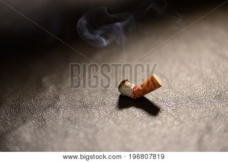 Lit cigarette butt with smoke on the ground