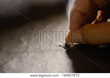 Hand pushing lit cigarette butt on the ground